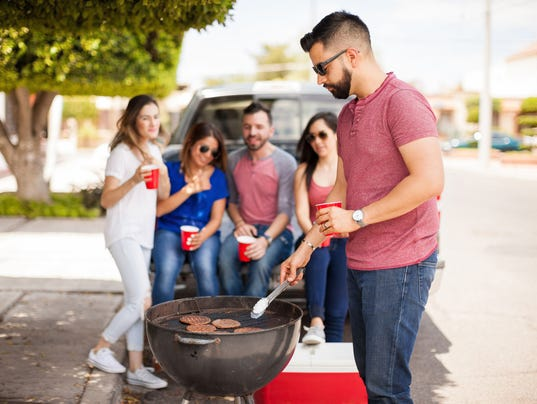 Young man with a beard grilling some burgers