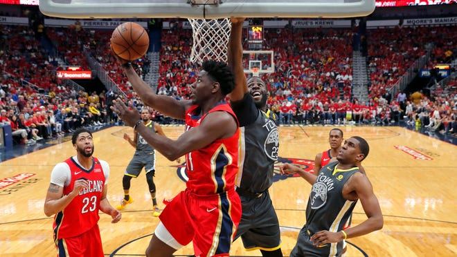 New Orleans Pelicans guard Jrue Holiday (11) goes to the basket against Golden State Warriors forward Draymond Green (23) in the first half of Game 4 of a second-round NBA basketball playoff series in New Orleans, Sunday, May 6, 2018. (AP Photo/Gerald Herbert)
