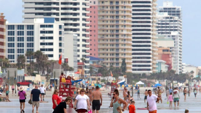Tourists play on the sand on Friday in Daytona Beach, where hoteliers have started to see guests return in bigger numbers on weekends. Still, challenges remain for Volusia County's tourism to rebound from the catastrophic downturn tied to the coronavirus pandemic.