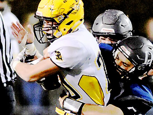 Red Lion running back Alex Keough (20) is tackled by a pair of Dallastown defenders during Friday night's game. The Lions defeated the Wildcats, 26-0.