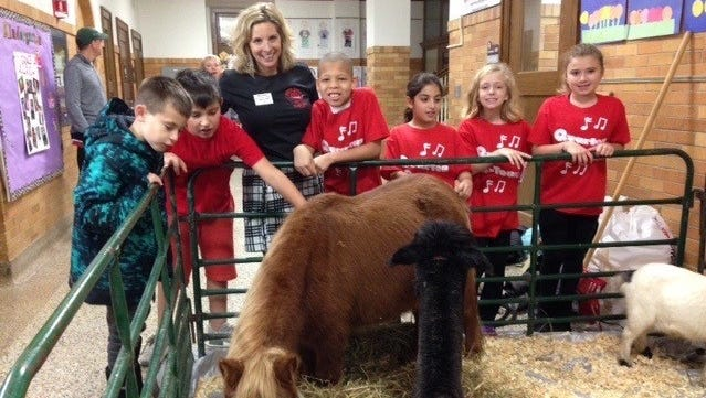 Quarton Principal Jill Ghiardi-Coignet enjoys the pony and llama in the petting zoo along with interested students. The petting farm was part of the celebration of the 90th year of the school's service to the community.
