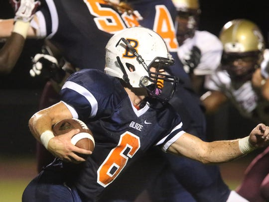 Blackman's Connor Mitchell (6) runs the option as he