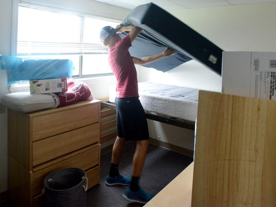 Incoming Union University freshman Mason Cagle sets up his mattress in his assigned room of his residence hall, Friday monring during freshman move-in day.