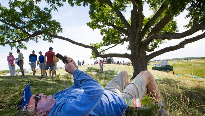 Tom Graham, of Orlando, Fla., waits for his son under one of the few trees  during Friday's second round of the U.S. Open golf tournament at Erin Hills.