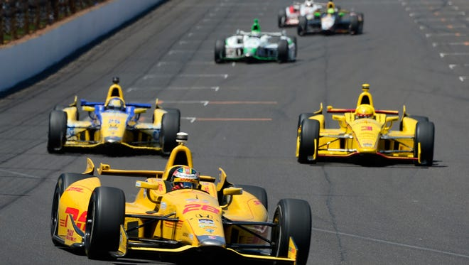 Ryan Hunter-Reay leads laps ahead of Helio Castroneves and Marco Andretti near the end of the Indianapolis 500 at the Indianapolis Motor Speedway. Sunday, May 25, 2014