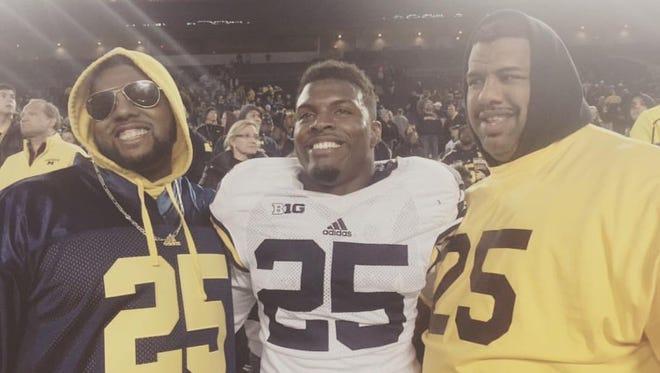 Michigan senior safety Dymonte Thomas, stands between his older brother, Jordan Washington, and father, Frank Thomas.