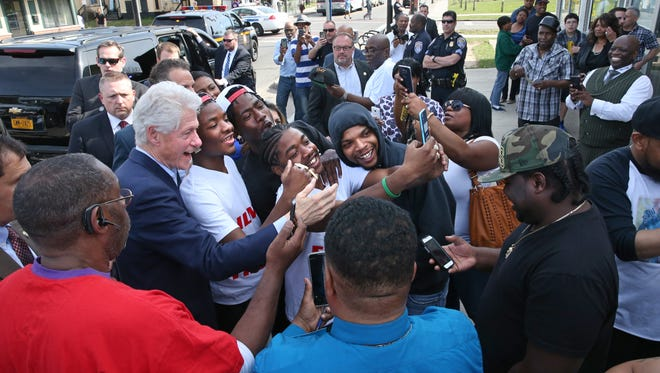 Former President Bill Clinton leans in to take the ultimate selfie with people outside New Creations Barber Shop on Jefferson Avenue during his visit to Rochester to campaign for his wife Hillary Clinton on April 18, 2016.