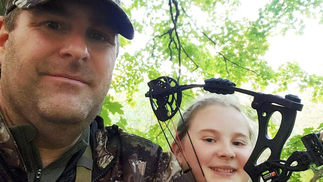 This photo taken Oct. 10, 2020, shows Zane Goucher, left, and daughter Annabelle Goucher bow hunting for deer near Dansville, Michigan. Zane Goucher says he hadn't gone hunting in 22 years but took up the sport again because the coronavirus outbreak provided incentive to spend more time outdoors with his children.