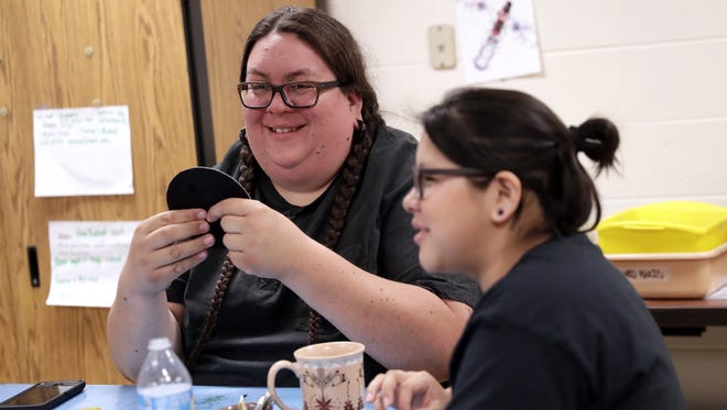 Benjamin Grignon, traditional Menominee art teacher at Menominee Indian High School in Keshena, works with students on bead projects. Grignon was recently named a Wisconsin 2019 High School Teacher of the Year.