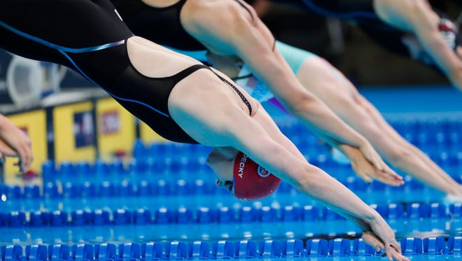 Katie Ledecky dives off the starting block during the women's 800-meter freestyle preliminary heats in the U.S. Olympic swimming team trials at CenturyLink Center.