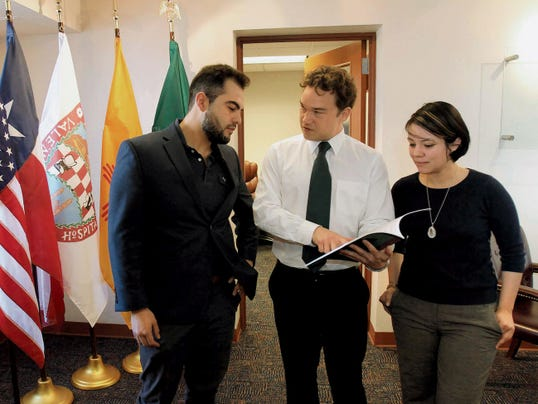 Research assistants José Angel Moreno and Cora Martinez look over the latest report generated by the Hunt Institute for Global Competitiveness with Executive Director Patrick Schaefer, center.
