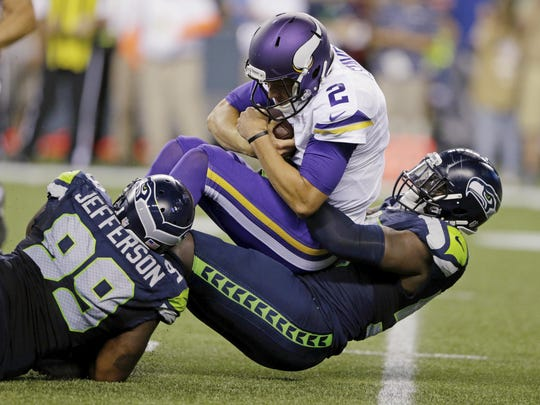 Minnesota Vikings quarterback Joel Stave (2) is sacked by Seattle Seahawks defensive end Frank Clark, right, and defensive tackle Quinton Jefferson (99) during the second half of a preseason game on Aug. 18 in Seattle.