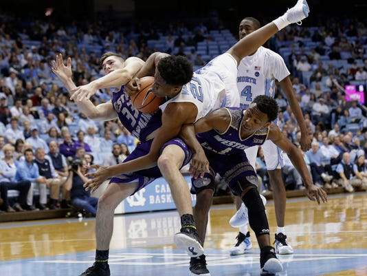 North Carolina's Sterling Manley (21) falls over Western Carolina's Onno Steger (33) and Desmond Johnson (1) during the first half of an NCAA college basketball game in Chapel Hill, N.C., Wednesday, Dec. 6, 2017. (AP Photo/Gerry Broome)