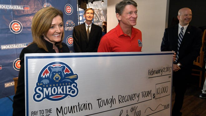 Ellen Wilhoit, left, executive director of Leadership Sevier, announced the launch of the Mountain Tough Recovery Team at the Smokies Stadium on Thursday afternoon during the Cubs World Series trophy tour. Wilhoit poses with Smokies owner Randy Boyd as he presented the initial $10,00 donation to the new charity. The Chicago Cubs organization donated another $10,000.