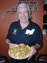 Jose Queredo, a co-owner in the restaurant, holds a