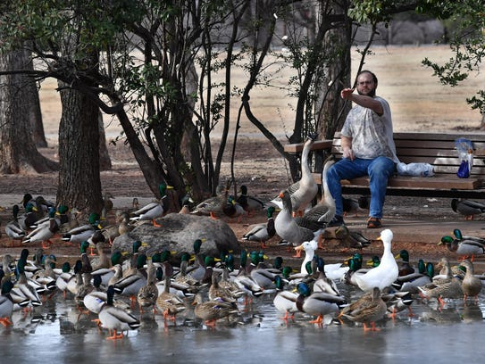 James Cozby feeds the ducks and geese at the Lucy Park