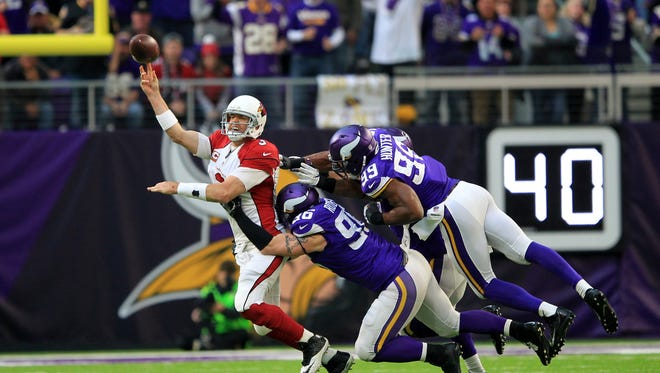 Arizona Cardinals quarterback Carson Palmer passes while getting pressured by Minnesota Vikings defenders Brian Robison (96) and Danielle Hunter (99) during the second half of an NFL football game Sunday, Nov. 20, 2016, in Minneapolis.