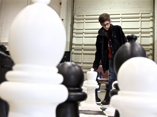 Jaymon Roussel mulls over his move of a queen piece during a chess game against his father Tom at the Old Fashion Christmas event at Oregon State Fairgrounds on Saturday, Nov. 19.