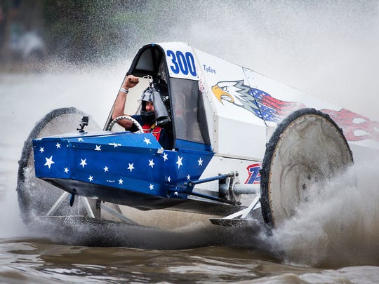 Tyler Johns throws his arms in the air as he crosses the finish line, winning the final race, during the Swamp Buggy Races Winter Classic on Sunday, January 28, 2018 at the Florida Sports Park in Naples, Fla.