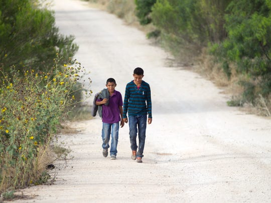 Two unaccompanied boys from Honduras walk along a dirt road coming from the Rio Grande near the Anzalduas International Bridge not far from the river in Mission, Texas on June 21. The boys sat down at the end of the road and waited till Border Patrol agents came and took them away in an SUV.