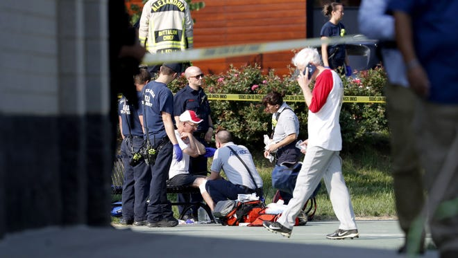 A person is treated by emergency workers  as members of the Republican congressional baseball team look on  following a shooting in Alexandria, Va  14 June 14, 2017. The Republican House majority whip Steve Scalise and at least four others have been shot shot at a congressional baseball game practice session, according to media reports