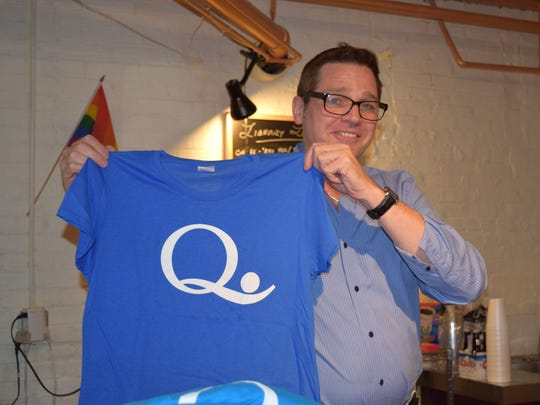 QSpot LGBT Community Center volunteer Tom Ludwiczak of Montclair displays a QSpot T-shirt at the refreshment counter on May 17 during the center's open house and dedication ceremony.