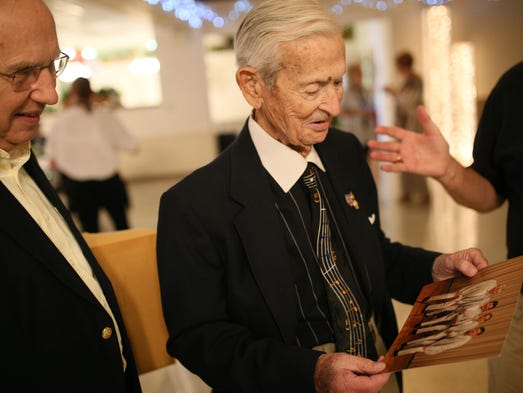 John Wearing, 92, of Detroit looks at an old photo