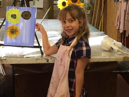 "Young artist Maia Bastianelli holds up her ""Sunflowers"" painting in the Mill Art Center and Gallery at Honeoye Falls."