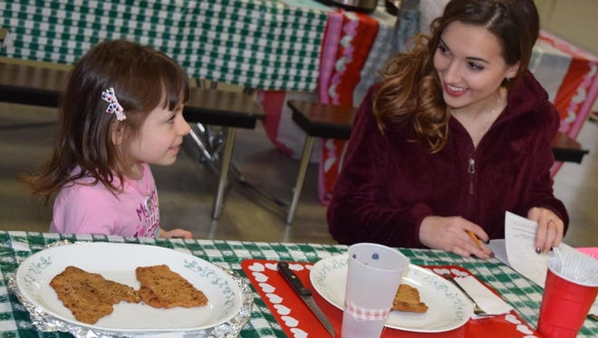 Heather Koering, an alumna of Cumberland County 4-H and a judge for this year's 4-H Favorite Food Contest, samples Amanda Cugino's entry. Amanda is a member of the Happy Kids 4-H Club.