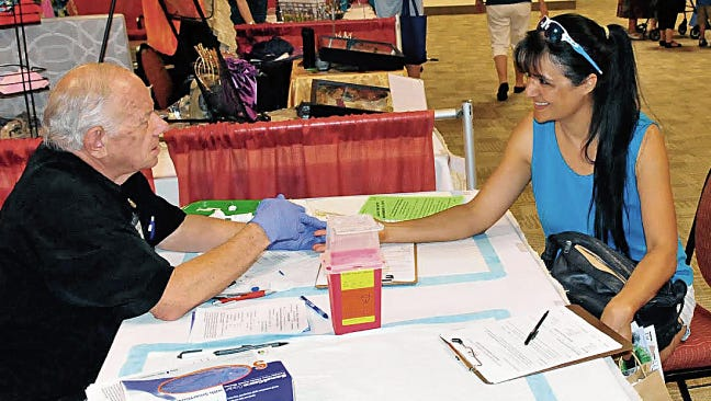Christina Johnson of La Mesa gets her sugar levels tested by Bob Donohoe of the Southern New Mexico Diabetes Outreach. His organization and many others provided tests and information at the 2015 Health and Fitness Expo at the Las Cruces Convention Center.