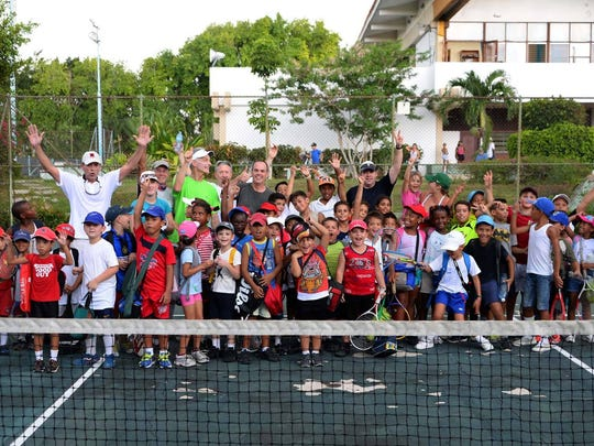 The kids and tennis coaches from Kids On the Ball-Cuba pose at the National Tennis Center in Havana in October 2015. In the background is the building that Jake Agna is hoping to renovate as part of his project.