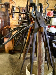 A row of blacksmithing tongs for handling hot metal.