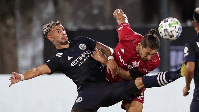 New York City FC midfielder Valentin Castellanos battles against Toronto FC defender Omar Gonzalez, right, during the second half of an MLS soccer match, Sunday, July 26, in Kissimmee, Fla.