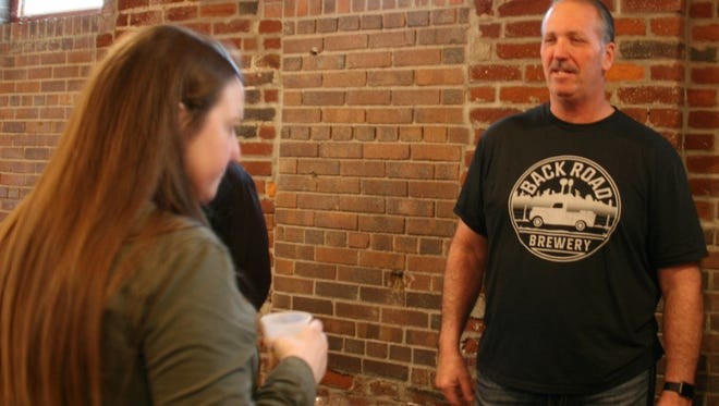 BackRoad Brewery's Eric Moorman serves up Sunny Daze at the Des Moines Register's tasting event after his beer made the final four in a bracket challenge.