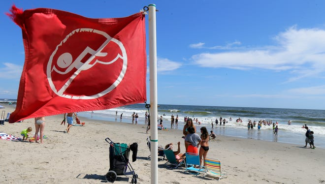 """Red flags mark areas of """"no swimming"""" in the ocean, where a hazard warning of potential rip currents has been issued, in Ocean Grove, NJ Tuesday August 30, 2016."""