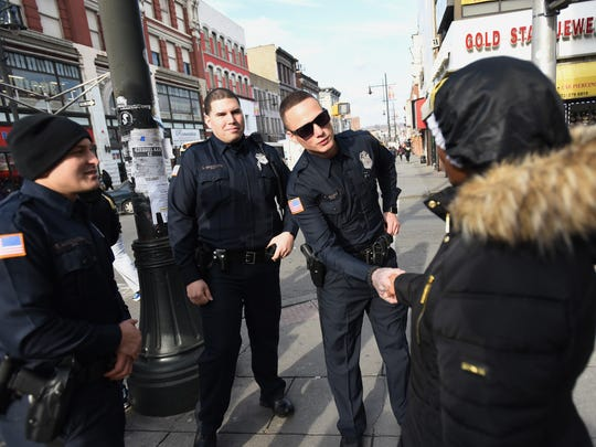 Three Paterson Police Officers (L to R) Ferdi Abedinoski, Salvador Brancato and Edward J. Akins who graduated from Police Academy last week,greet Paterson resident Cassandra Byrd during their patrols for the first time in commercial shopping districts in downtown Paterson on 12/19/17.
