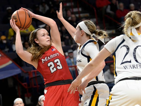 Marist guard Rebekah Hand is defended by Quinnipiac guard Carly Fabbri and teammate forward Paige Warfel during the MAAC tournament championship in Albany in March.