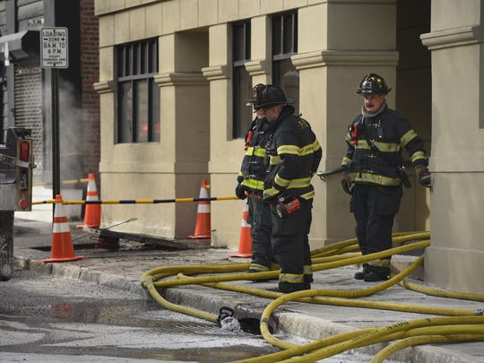 Firefighters on Catharine Street stand over a hose