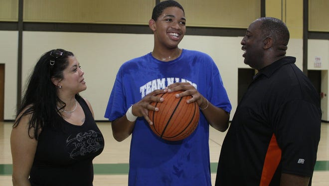 As an eighth-grader in 2011, Karl-Anthony Towns talks with his mother Jacqueline Cruz-Towns and father Karl Towns Sr.