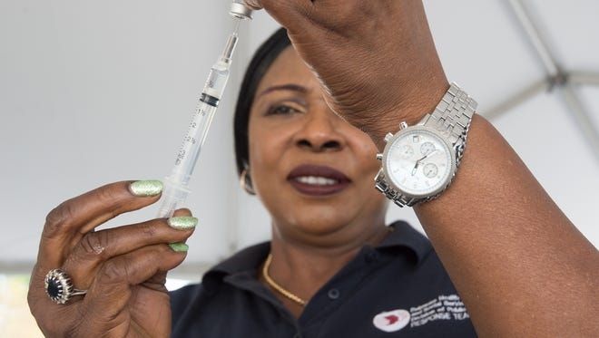 Helen Madukwe, a registered nurse with the Division of Public Health, prepares a flu vaccination at their drive-thru flu vaccination clinic at the DelDOT Administration Building in Dover.