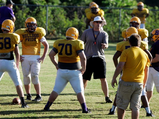 Smyrna football coach Matt Williams talks to his offensive line during practice on Monday.
