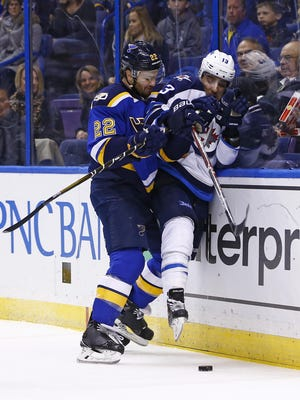 Winnipeg Jets' Brandon Tanev, right, is checked off of the puck by St. Louis Blues' Kevin Shattenkirk during the first period Saturday.