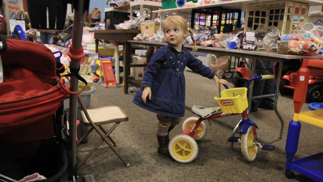 File photo: Alyssa George, then 2, of Attica looks up at her mom, Trina, who had just called her.  Alyssa was playing with the toys at the Ronald McDonald House Charities Household & Antiques Sale on Oct. 14, 2010.