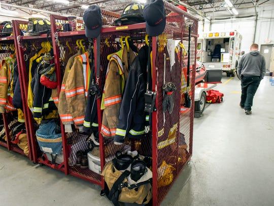 Firefighters' gear hangs in lockers by the door, ready