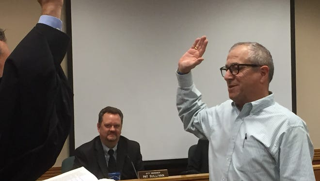 Freshman Northville Councilman Patrick Giesa takes the oath of office, administered by Judge James Plakas, at City Hall on Monday. Looking on is City Manager Patrick Sullivan.