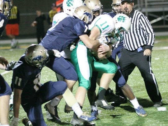 Margaretta's Logan Graffin drags two St. Mary Central Catholic defenders into the secondary in a game last season.