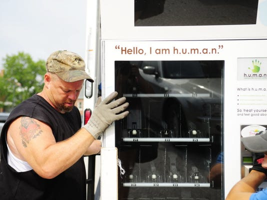 Burn Enterprises delivery company owner Bob Burn and his son and employee Ryan Krepps work to load a new vending machine off the truck behind York Suburban High School in August 2012. The school replaced its former Pepsi and snack vending machines with vending machines that will be stocked with healthier options, such as pita chips, fruit smoothies and soy milk. (DAILY RECORD/SUNDAY NEWS - CHRIS DUNN)