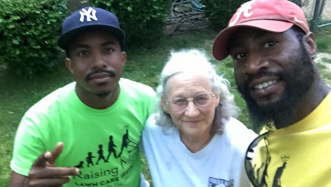 Rodney Smith and Terrence Stroy pose with a woman who needed help with her lawn.