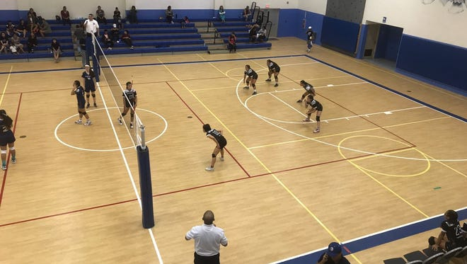 The Sharks get ready to receive a serve from the Eagles in an IIAAG Girls Volleyball game on Tuesday night at Harvest.