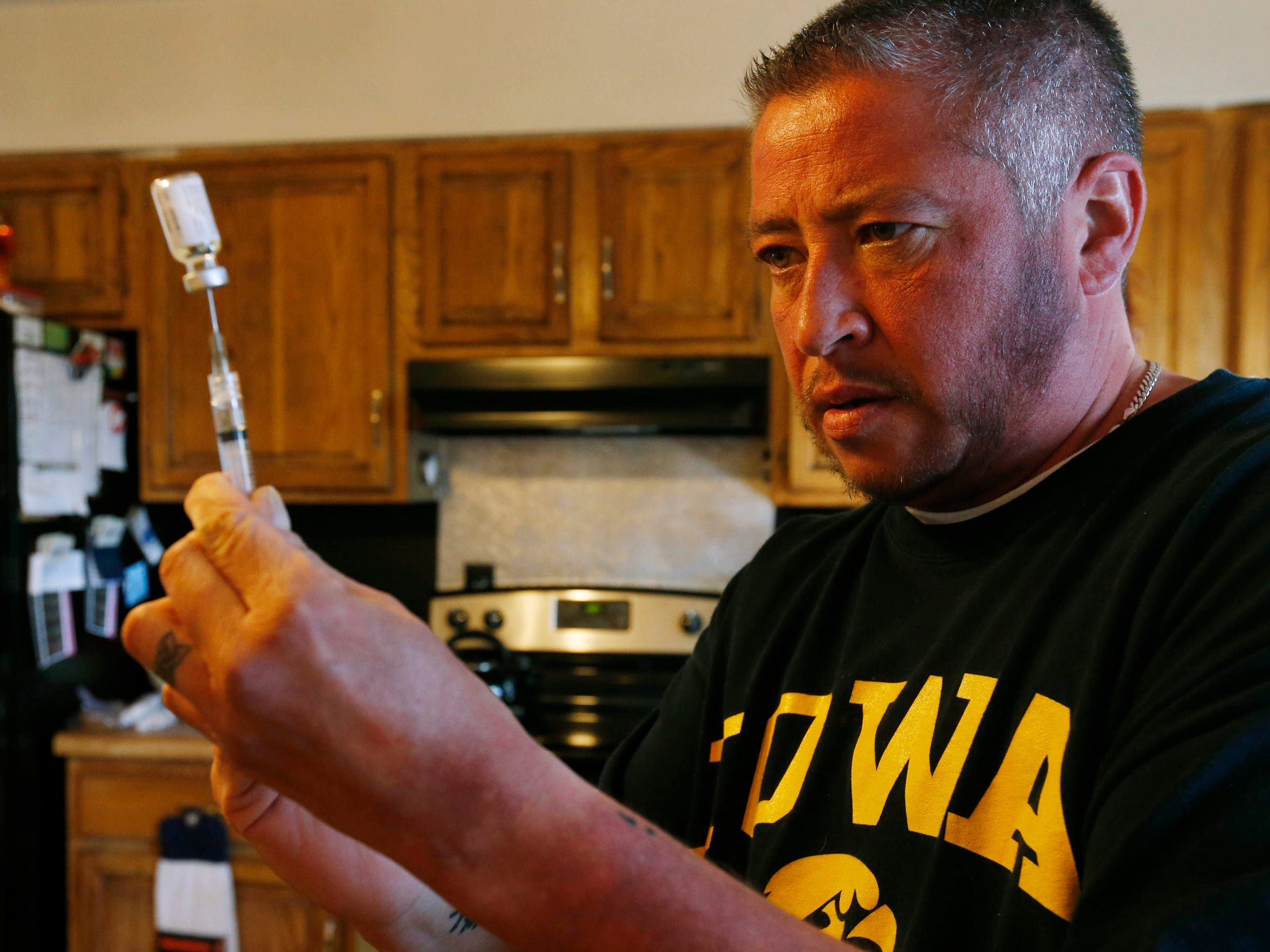 Aiden DeLathower gets ready to inject himself with testosterone Sunday, Nov. 6, 2016, in the kitchen of his home in Davenport.